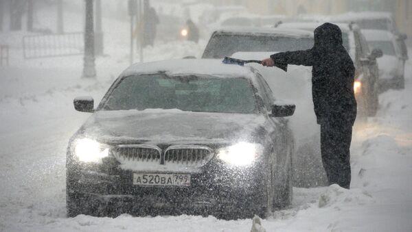 Владелец отчищает свою машину от налипшего снега во время снегопада в Москве, архивное фото - Sputnik Таджикистан
