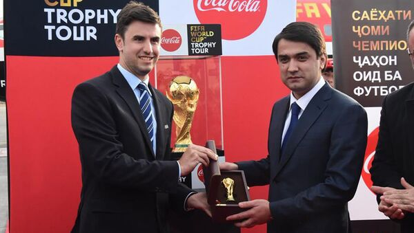 Рустам Эмомали демонстрирует кубок чемпионата мира по футболу в Таджикистане - Sputnik Тоҷикистон