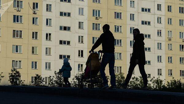 Мужчина и женщина с ребенком идут по тротуару. Архивное фото - Sputnik Тоҷикистон
