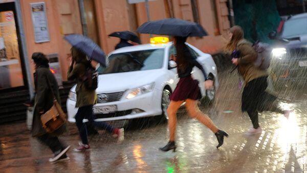 Пешеходы на улице в Москве во время сильного дождя. - Sputnik Таджикистан