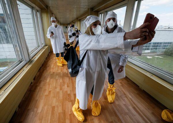 Журналисты фотографируются во время посещения Чернобыльской АЭС - Sputnik Таджикистан