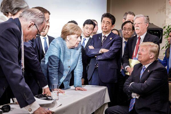 Саммит G7 в Квебеке, который обернулся скандалом. Яркая фотография с Меркель, которая давит на Дональда Трампа, стала вирусной. Июнь 2018 года. - Sputnik Таджикистан