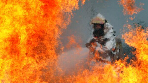 Пожарный тушит огонь, архивное фото - Sputnik Таджикистан