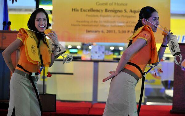 Стюардессы авиалиний Cebu Pacific танцуют во время мастер-класса по безопасности на борту самолета в аэропорте Манилы - Sputnik Таджикистан