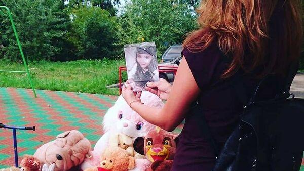 Девушка держит фотографию убитой девочки на мемориале - Sputnik Таджикистан