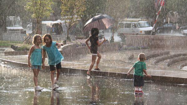Дети играют под дождем, архивное фото - Sputnik Тоҷикистон