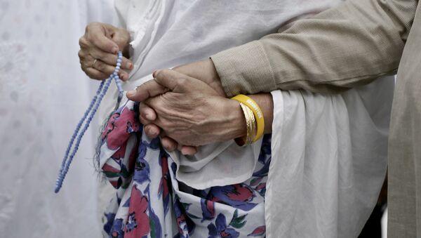 Пожилая мусульманка держит за руку своего мужа во время хаджа, архивное фото - Sputnik Тоҷикистон