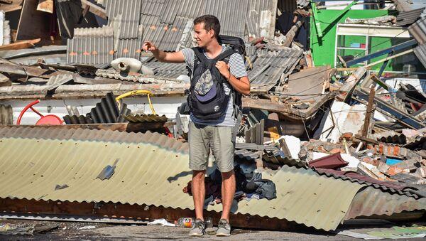 Турист пытается поймать машину после землетрясения на острове Ломбок в Индонезии - Sputnik Таджикистан