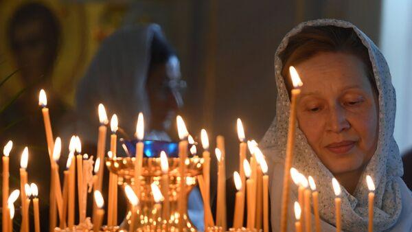 Верующая во время божественной литургии - Sputnik Таджикистан