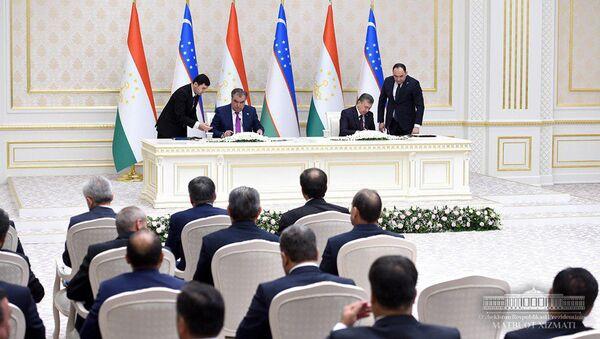 Президент Таджикистана Эмомали Рахмон и Президент Узбекистана Шавкат Мирзиёев подписывают документы - Sputnik Тоҷикистон
