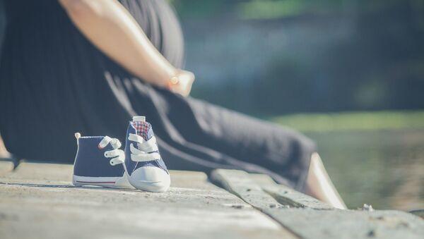 Беременная девушка сидит в парке, архивное фото - Sputnik Таджикистан