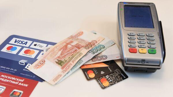 Терминал оплаты банковскими картами и денежные купюры, архивное фото - Sputnik Таджикистан