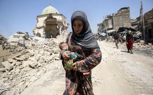 Женщина с ребенком бежит из Мосула во время наступления иракских правительственных сил на боевиков ИГ - Sputnik Таджикистан