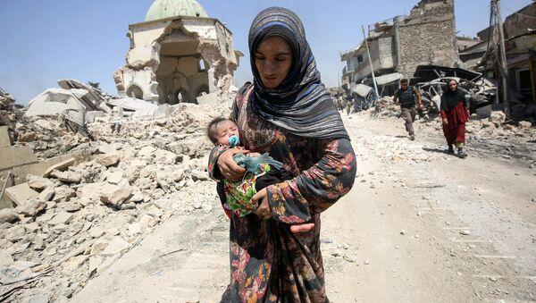 Иракская женщина с ребенком напротив разрушенной мечети Аль-Нури в Мосуле - Sputnik Таджикистан
