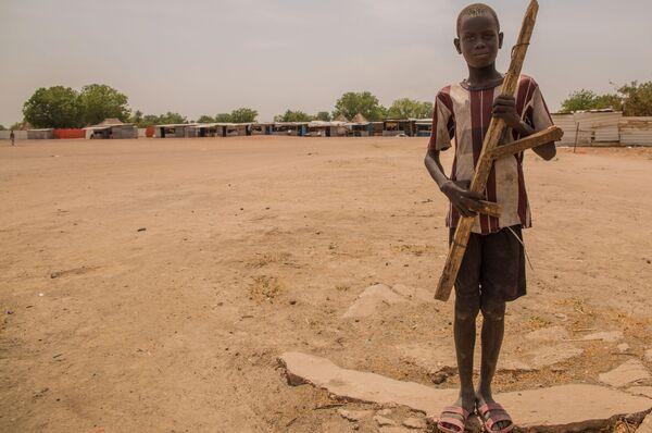 Мальчик с деревянным ружьем в голодающей деревне, Судан - Sputnik Таджикистан