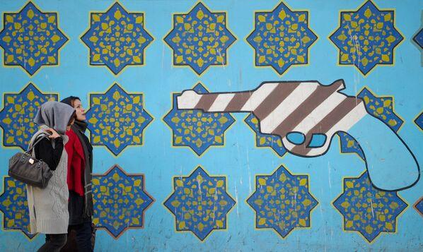 Женщины идут вдоль стены здания бывшего посольства США в Тегеране - Sputnik Таджикистан