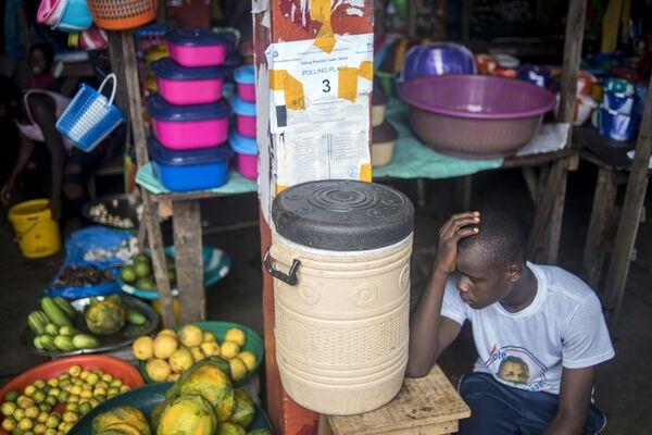 Мужчина в ожидании оглашения результатов выборов на рынке в Монровии, Либерия - Sputnik Таджикистан