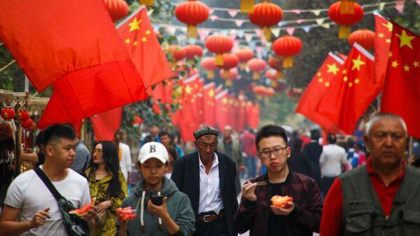 Люди проходят мимо китайских флагов в Кашгаре, Синьцзян-Уйгурский автономный район, Китай - Sputnik Таджикистан