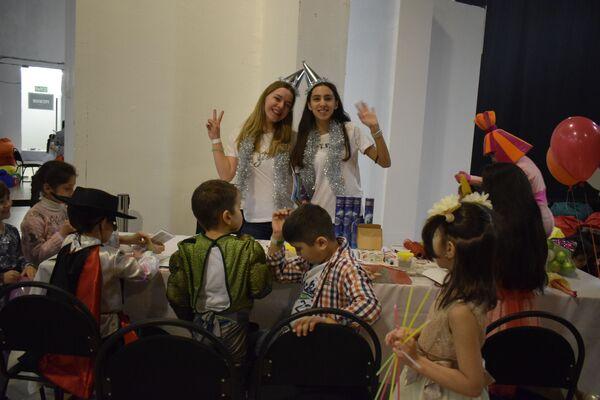 В организации праздника таджикскому культурному центру активно помогали добровольцы. Так, две участницы команды Памирской лиги КВН  Кофе с молоком учили детишек делать новогодние украшения и аппликации - Sputnik Таджикистан