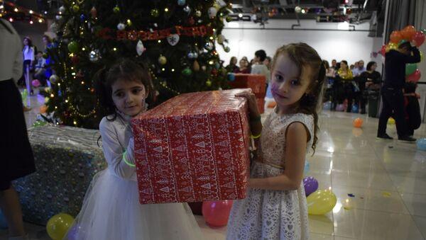 А две девочки, решив что есть вещи поинтересней театрального представления, решили проверить на прочность бутафорские подарки у елки. Но все таки лучшим подарком для ребят стала сама атмосфера праздника, созданная НУР, а для родителей - веселье и радость на лицах сыновей и дочек  - Sputnik Таджикистан