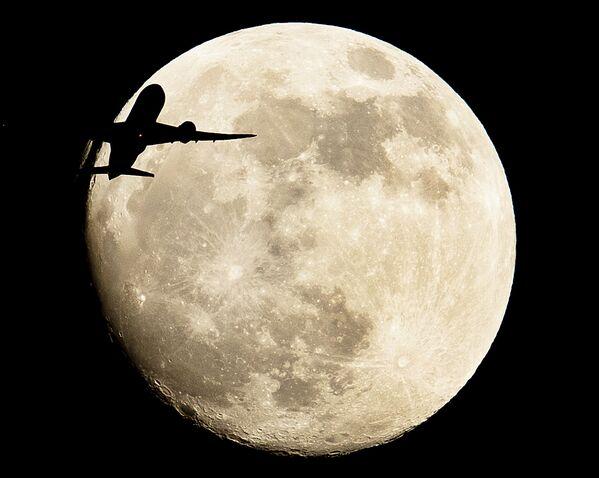 Самолет пролетает на фоне луны в Германии  - Sputnik Таджикистан