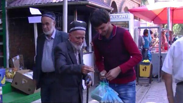 Молодой человек помогает на рынке пенсионеру, архивное фото - Sputnik Таджикистан