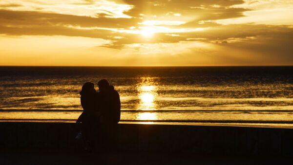 Молодые люди встречают закат на пляже, архивное фото - Sputnik Тоҷикистон
