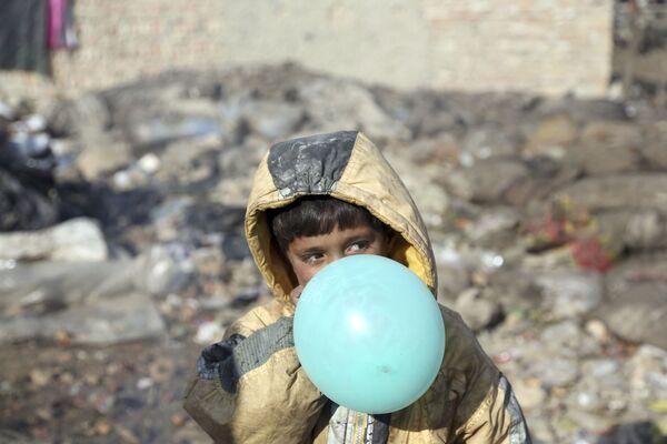 Афганский мальчик надувает воздушный шарик, окраина Кабула, Афганистан, 2017 год - Sputnik Таджикистан