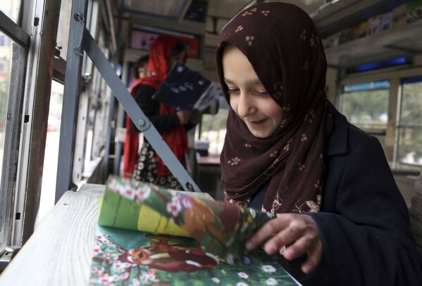 Девочки читают книги в передвижной библиотеке в Кабуле - Sputnik Таджикистан