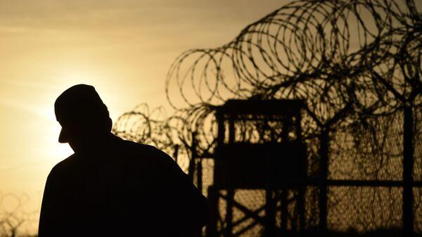 Cолдат, идущий рядом с забором с колючей проволокой - Sputnik Таджикистан