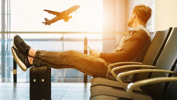 Молодой человек в аэропорту в зале ожидания - Sputnik Тоҷикистон