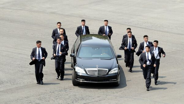 Северокорейские телохранители бегают трусцой рядом с автомобилем с лидером Северной Кореи Ким Чен Ыном - Sputnik Таджикистан
