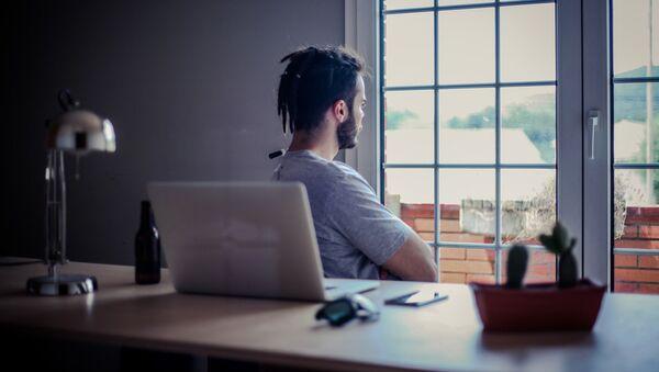 Мужчина смотрит в окно у рабочего стола - Sputnik Тоҷикистон