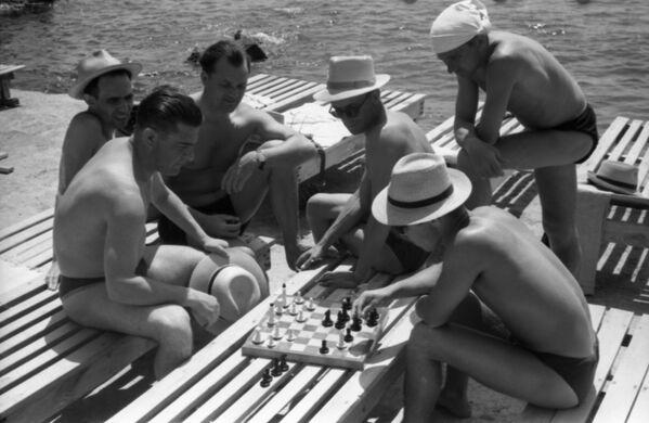 На пляже ялтинского санатория Украина отдыхающие играют в шахматы, 1958 год - Sputnik Таджикистан