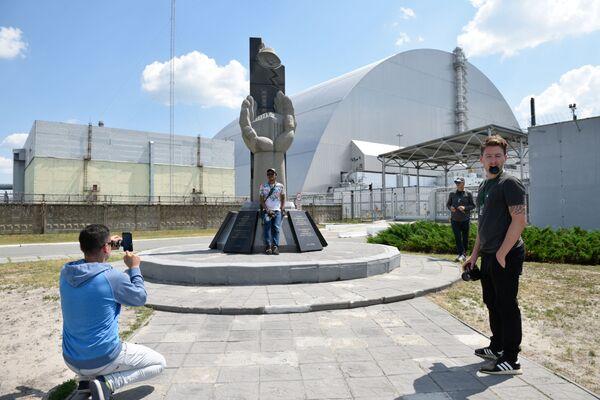 Туристы фотографируются возле памятника ликвидаторам аварии на Чернобыльской атомной электростанции имени Владимира Ильича Ленина  во время экскурсии в зону отчуждения в городе Чернобыле - Sputnik Таджикистан