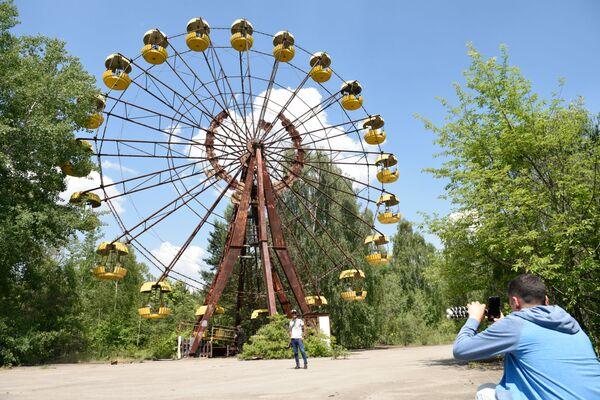 Туристы во время экскурсии в зону отчуждения Чернобыльской атомной электростанции (ЧАЭС) имени Владимира Ильича Ленина в городе Припяти - Sputnik Таджикистан