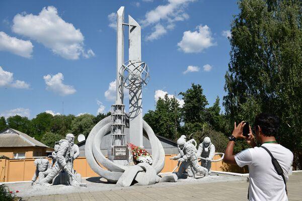 Туристы фотографируют монумент пожарным Тем, кто спас мир во время экскурсии в зону отчуждения ЧАЭС - Sputnik Таджикистан