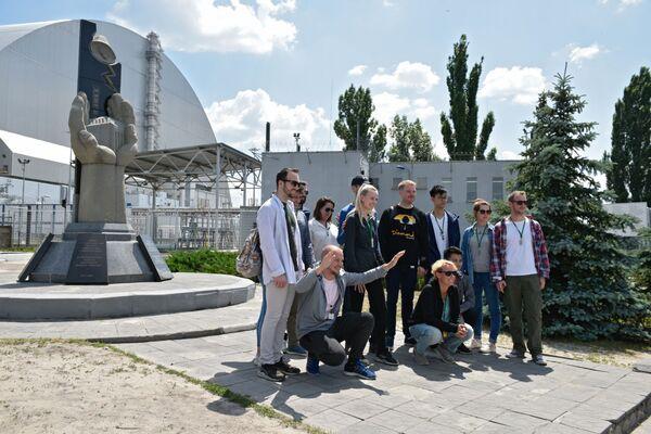 Туристы фотографируются возле памятника ликвидаторам аварии на ЧАЭС  во время экскурсии в зону отчуждения в городе Чернобыле - Sputnik Таджикистан