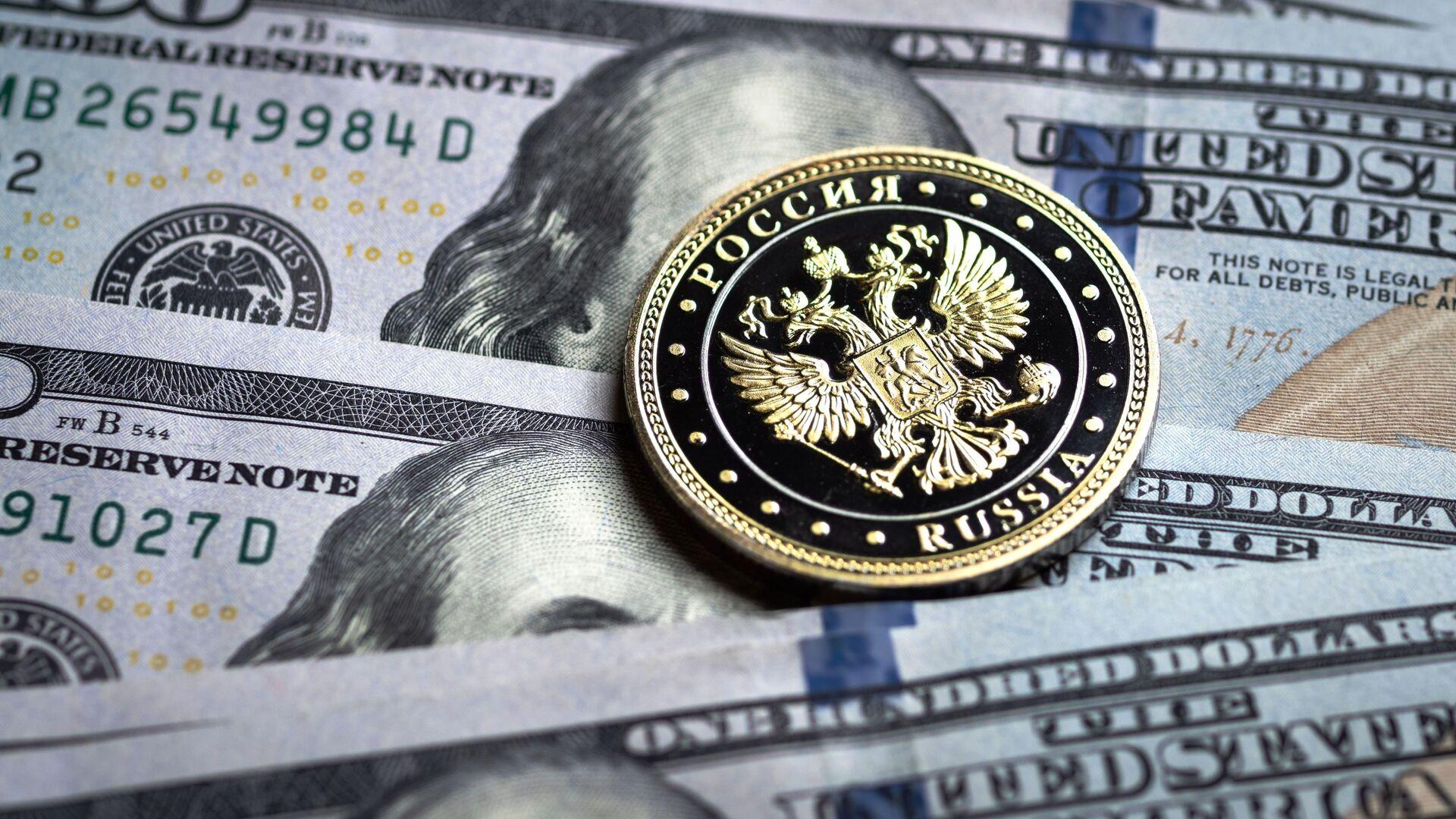 Купюры американских долларов и монета с гербом Российской Федерации - Sputnik Тоҷикистон, 1920, 11.10.2021