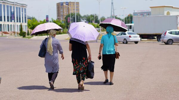 Женщины идут с зонтиками спасаясь от солнца - Sputnik Тоҷикистон