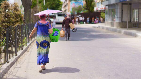 Женщина идет с зонтиком защищаясь от солнца - Sputnik Таджикистан
