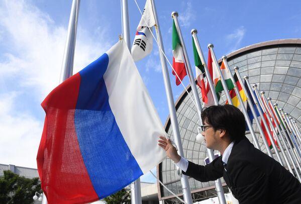 Вывешивание флага России у международного выставочного центра INTEX Osaka перед открытием саммита Группы двадцати в японской Осаке - Sputnik Таджикистан