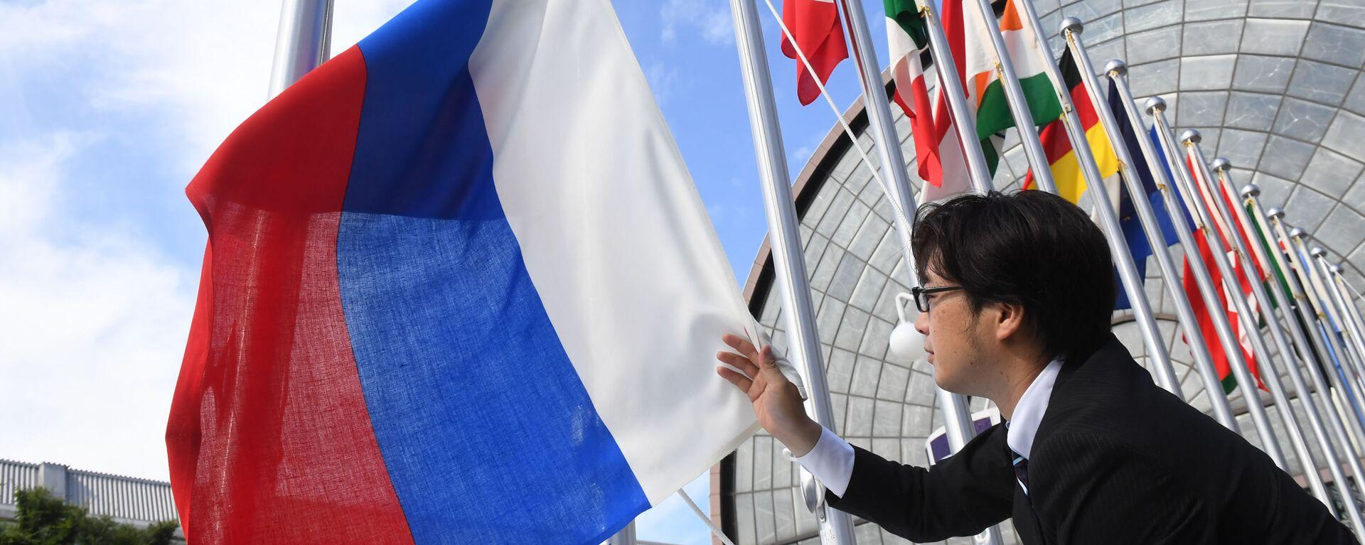 Вывешивание флага России у международного выставочного центра INTEX Osaka перед открытием саммита Группы двадцати в японской Осаке - Sputnik Таджикистан, 1920, 05.09.2021