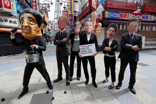 Протестующие в масках мировых лидеров во время саммита G20 в Осаке, Япония - Sputnik Таджикистан