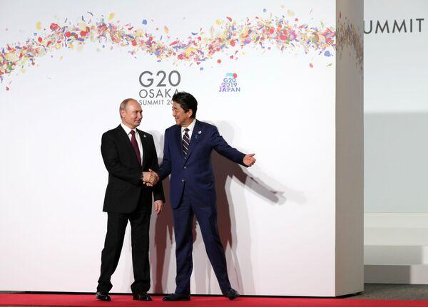 Президент РФ Владимир Путин и премьер-министр Японии Синдзо Абэ на церемонии официальной встречи участников саммита Группы двадцати в международном выставочном центре INTEX Osaka - Sputnik Таджикистан