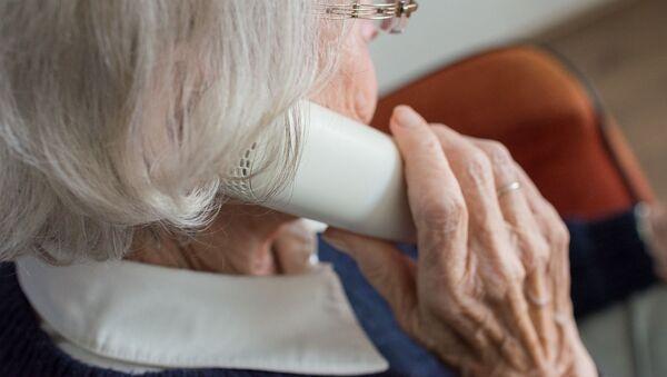 Пожилая женщина звонит по телефону, архивное фото - Sputnik Таджикистан