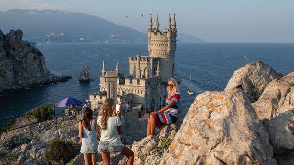 Отдыхающие фотографируются возле замка Ласточкино гнездо на береговой скале в поселке Гаспра в Крыму - Sputnik Таджикистан