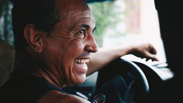 Мужчина за рулем автомобиля смеется - Sputnik Таджикистан