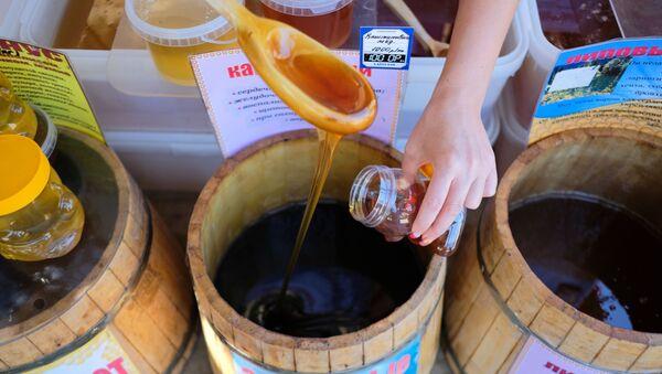 Продавец наливает мед в банку, архивное фото - Sputnik Тоҷикистон