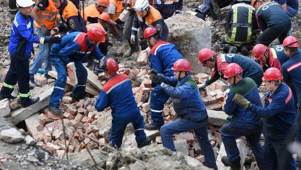 Сотрудники МЧС РФ и рабочие разбирают перекрытия, рухнувшие в строящемся здании в Новосибирске - Sputnik Тоҷикистон